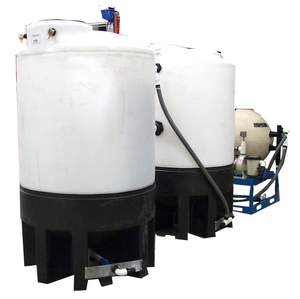 An alkaline wash water system for cleaning metal-working oil and scale from metal parts including a heated wash water recirculation system in which a small portion of the
